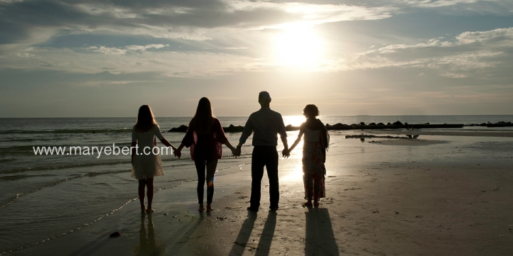 Silhouette of family on beach for family portraits